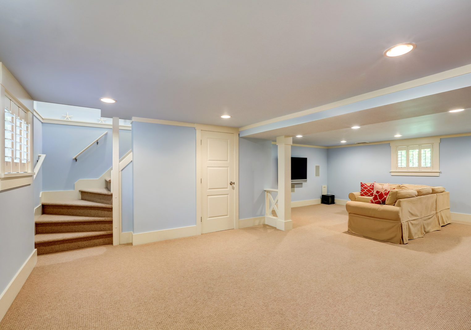 Spacious basement room interior in pastel blue tones. Beige carpet floor and large corner sofa with TV. Northwest USA
